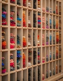 Dans des étagères de chêne clair, les gants aux couleurs chatoyantes s'empilent, créant de vibrantes harmonies...